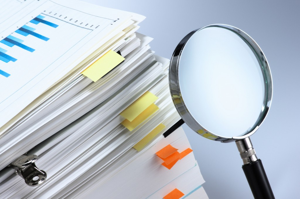 Magnifying glass showing editing of business documents