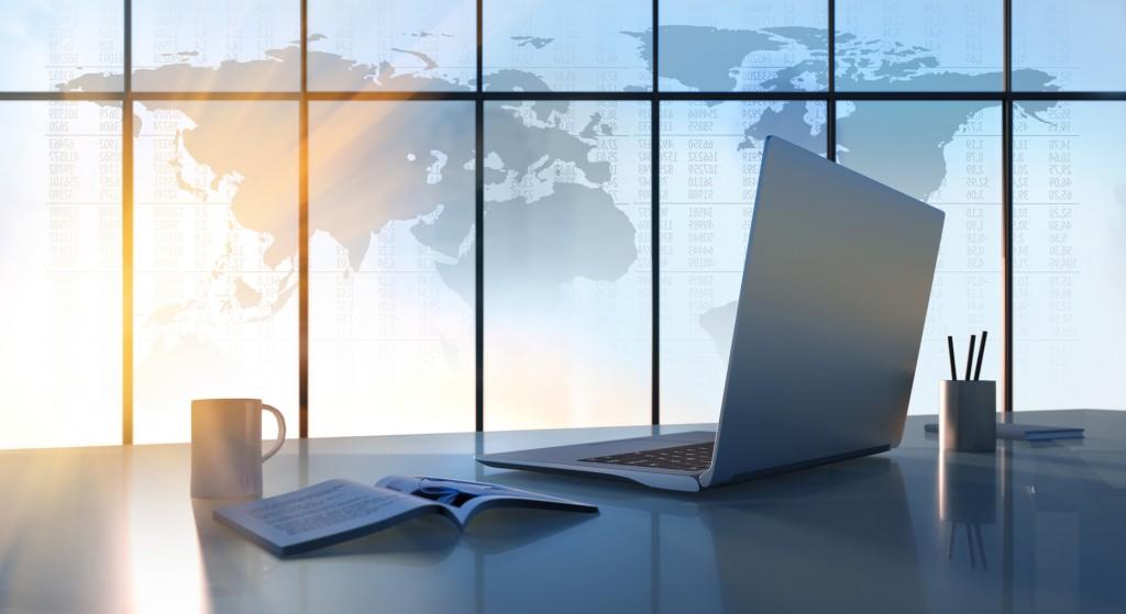 Laptop auf Schreibtisch mit Weltkarte für Übersetzung